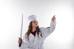 有一把大刀子的女孩厨师 免版税库存照片