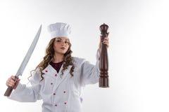 有一把大刀子的女孩厨师 免版税图库摄影