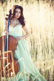有一把大提琴的女孩在一棵高草 库存图片