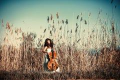 有一把大提琴的女孩在一棵高草 图库摄影