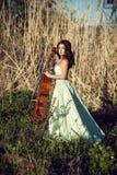 有一把大提琴的女孩在一棵高草 免版税图库摄影
