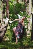 有一把小提琴的一个美丽的女孩在一件长的礼服在树中盘旋 免版税库存照片