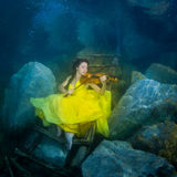 有一把小提琴的女孩在水下 免版税库存图片