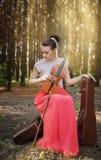有一把小提琴的美丽的女孩在森林里 库存照片