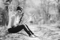 有一把小提琴的美丽的女孩在他的手上 库存照片