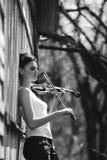 有一把小提琴的美丽的女孩在他的手上 免版税库存照片
