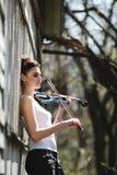 有一把小提琴的美丽的女孩在他的手上 免版税库存图片