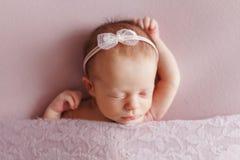 有一把弓的一个逗人喜爱的新出生的女孩在她的头睡着在桃红色后面 库存图片