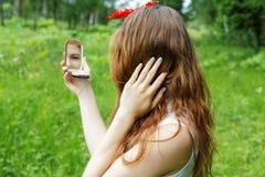 有一把弓的女孩在她的调查镜子的头 库存图片