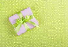 有一把弓的淡紫色礼物盒在浅绿色的背景 充满惊奇的箱子在圆点背景 库存图片