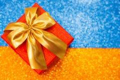 有一把弓的红色礼物盒在颜色闪耀的背景 免版税库存图片