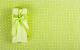 有一把弓的黄色礼物盒在浅绿色的背景 充满惊奇的箱子在圆点背景 免版税库存照片