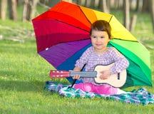 有一把彩虹伞和吉他的小愉快的女孩在公园 库存照片