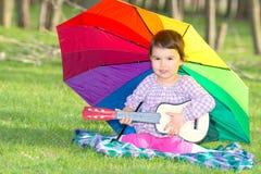 有一把彩虹伞和吉他的小愉快的女孩在thepark 库存图片
