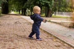 有一把拉长的双刃剑的逗人喜爱的小孩 滑稽的男婴在有一把被生动描述的锐剑的公园 图库摄影