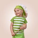 有一把木匙子的微笑的儿童厨师 免版税库存图片