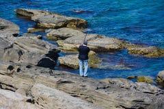 有一把标尺的渔夫在岩石在海 免版税库存图片