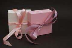 有一把桃红色弓的两个礼物盒在布朗背景 礼物,生日 概念玻璃现有量扩大化的销售额 复制文本的空间 库存照片