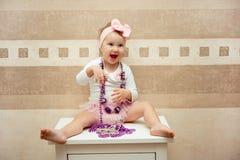 有一把桃红色弓的美丽的矮小的愉快的女孩 免版税库存照片