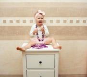 有一把桃红色弓的美丽的矮小的愉快的女孩 库存图片
