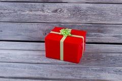 有一把浅绿色的弓的红色礼物盒 库存图片