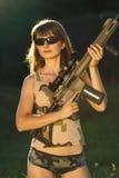 有一把猎枪的年轻美丽的女孩在室外 库存照片