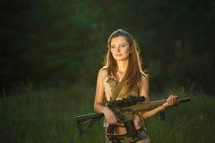 有一把猎枪的年轻美丽的女孩在室外 免版税库存图片