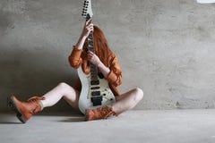 有一把电吉他的年轻红发女孩 岩石音乐家gir 免版税库存照片