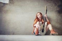 有一把电吉他的年轻红发女孩 岩石音乐家gir 免版税图库摄影