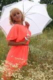 有一把白色伞的,一件长的礼服,花的领域,一件桃红色礼服女孩 花的领域的美丽的白肤金发的女孩 库存照片