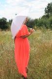 有一把白色伞的,一件长的礼服,花的领域,一件桃红色礼服女孩 花的领域的美丽的白肤金发的女孩 图库摄影