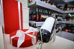 有一把白色弓的一个红色礼物盒和一个瓶酒 免版税库存照片