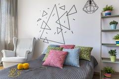 有一把白色扶手椅子的时髦的卧室 库存图片