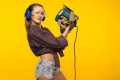 有一把竖锯的年轻女工匠在黄色背景前面 免版税库存图片