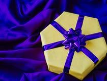 有一把紫色弓的黄色礼物盒 免版税图库摄影