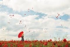 有一把红色伞的一个女孩在旋转在天空中的鸦片的一个红色鸦片领域和红色瓣 免版税库存图片