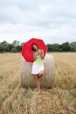 有一把红色伞的一名妇女 图库摄影