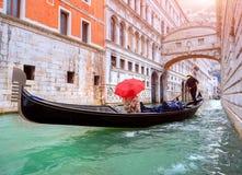 有一把红色伞的妇女在通过在叹气桥梁的长平底船在威尼斯 库存图片