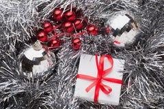 有一把红色弓的白色礼物盒在银色诗歌选 库存照片