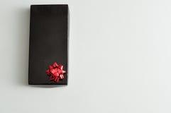 有一把红色弓的黑礼物盒 库存照片