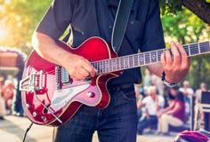 有一把红色电吉他的人在播放音乐会的公园 免版税库存照片