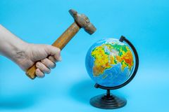 有一把老生锈的锤子的男性手,在地球的摇摆 免版税库存图片