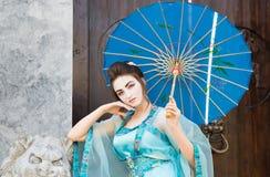 有一把蓝色伞的美丽的艺妓 免版税库存照片