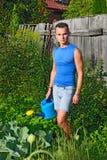 有一把蓝色喷壶的一个年轻人在有cabb的庭院附近 库存照片