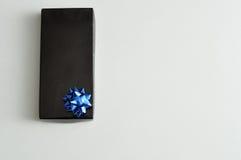 有一把蓝色弓的黑礼物盒 免版税库存图片