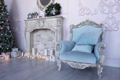 有一把蓝色扶手椅子、壁炉和圣诞树的演播室 免版税库存图片