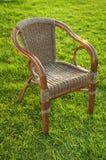 有一把藤椅的草草坪 免版税库存图片