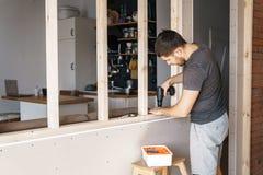 有一把螺丝刀的一个人在他的手上在他的房子里修理一个窗口的一个木制框架 免版税库存照片