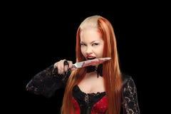 有一把血淋淋的刀子的可爱的吸血鬼 免版税库存照片