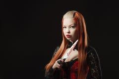 有一把血淋淋的刀子的可爱的吸血鬼 免版税库存图片